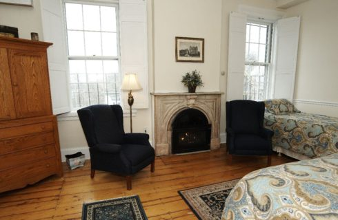 Spacious room with a fireplace and two wingback chairs and a king and twin bed.