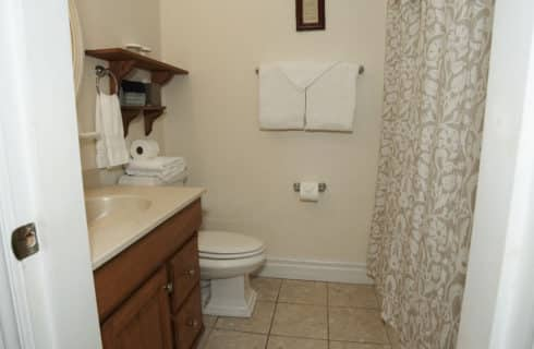 Bathroom with wooden cabinet vanity and a floral shower curtain.