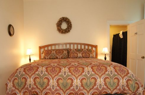 Large king sized bed made up with a bright patterned spread with two night tables in a room with cream walls.