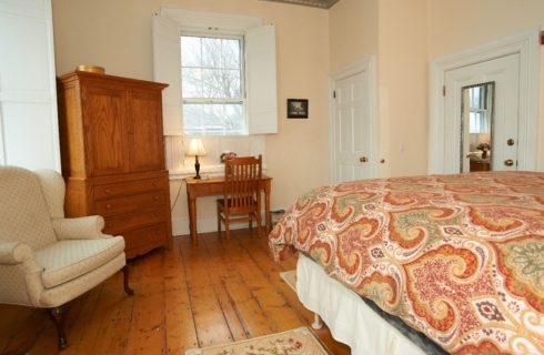 Guest room with wooden floors, a table and armoise in cherry and a king sized bed.