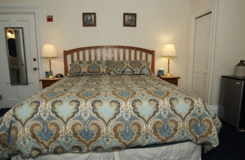 Large king sized bed made up in a blue and tan paisley comforter.