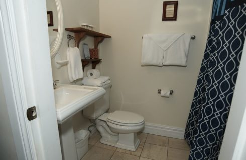 White bathroom with a pedestal sink, stool and brown shower curtain.