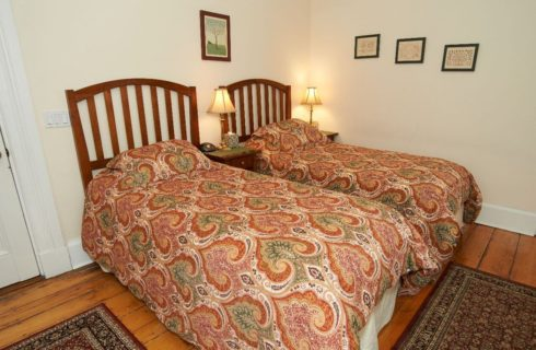 Twin beds made up in orange paisley covers with nightstands and lamps.