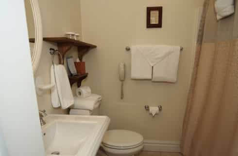 Bathroom with a white pedestal sink and stool and a tan shower curtain.