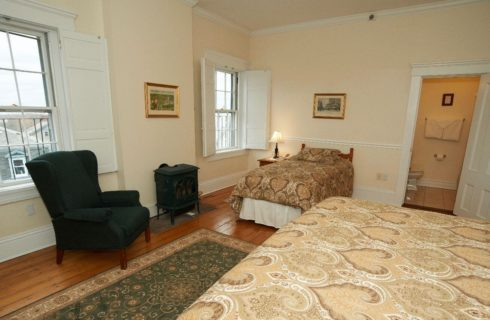 Large bright room with a king and a twin bed facing shuttered windows and a wingback chair.