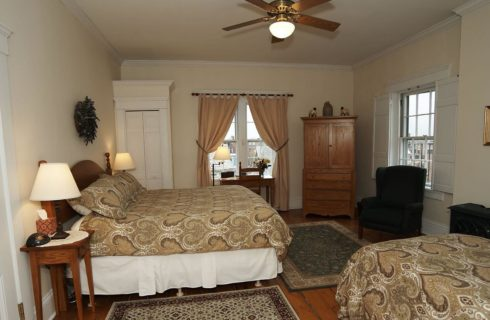 King and twin bed in a room with a wooden armoire, windows and a ceiling fan.
