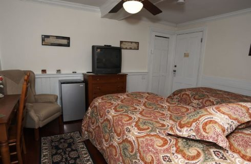 Room made up with twin beds facing dresser, TV and mini-fridge.