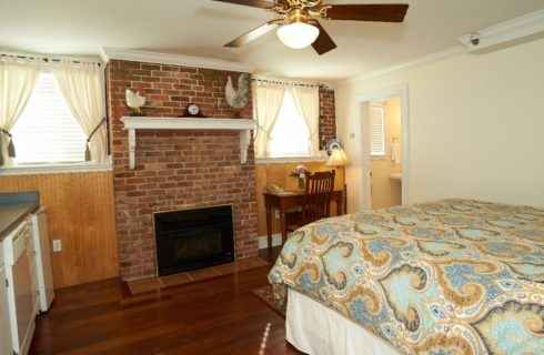 King bed with paisley comforter in a room with a brick fireplace and ceiling fan.