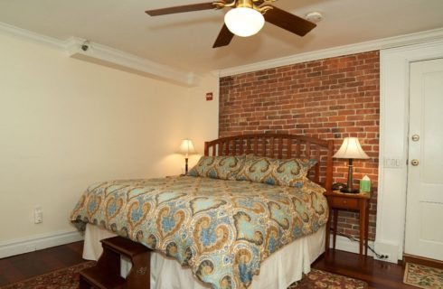 King bed with paisley comforter in a room with a brick accent wall and ceiling fan.