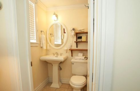 Bathroom win white with a pedestal sink and white shower curtain.