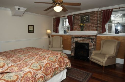 King bed made up in a paisley bedspread in a room with a fireplace and a ceiling fan.