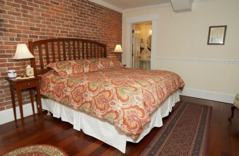 Big king sized bed in a room with a brick accent wall and adjoining bathroom.