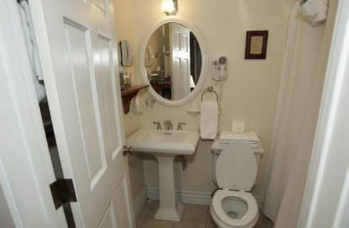 Bathroom in white with a pedestal sink, stool and shower.