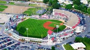 A large open top baseball field with green grass and lots of parking.