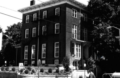 Black and white vintage photo of a large 3-story brick building on a city corner street.