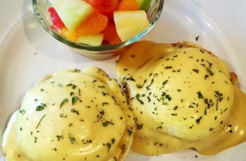 Eggs Benedict on a white plate with a bowl of fresh fruit salad.