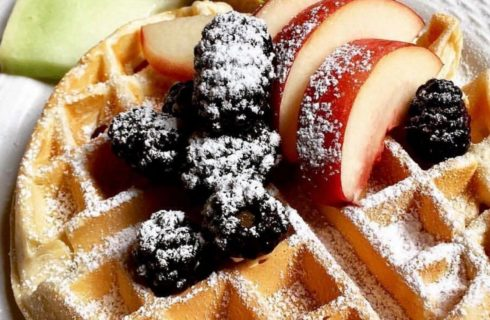 Belgian waffle topped with cherries and plum slices and dusted with powdered sugar.
