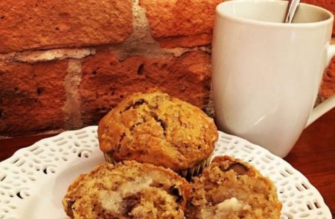 Three fresh muffins on a white plate accompanied by a hot beverage.