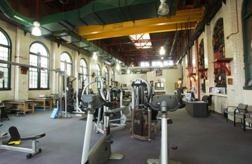 Gym machines cover the floor of a gym with big arched windows.