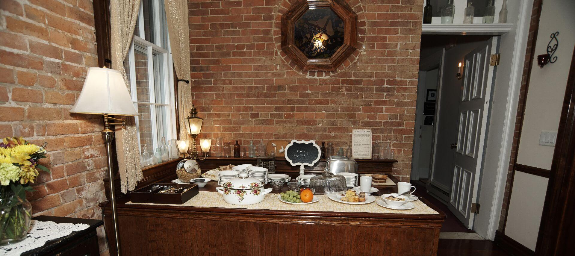 Breakfast buffet with fruit, pastries, cereal and plates and cutlery.