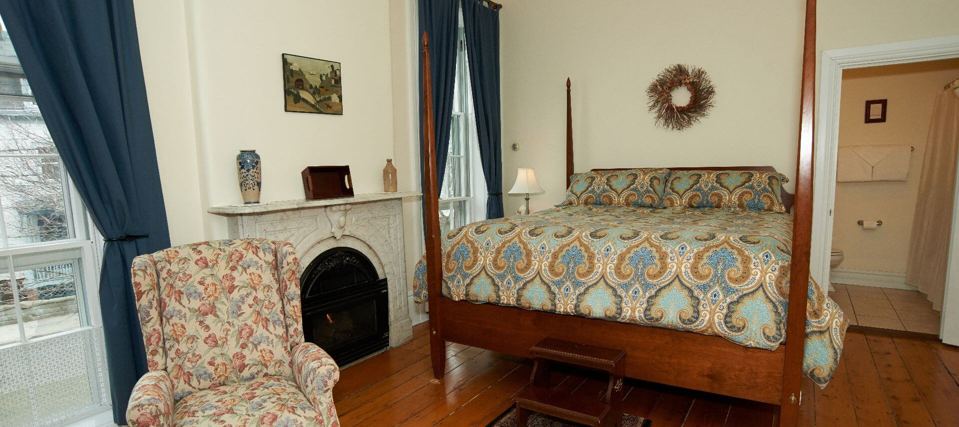LArge king four-post bed next to fireplace and large window with a wing back chair.