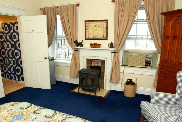Charming bedroom with a queen bed, small fireplace and two big bright windows.