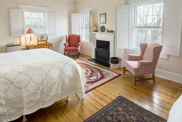 King and twin beds in a spacious bedroom with a wooden armoire and red wing back chairs.