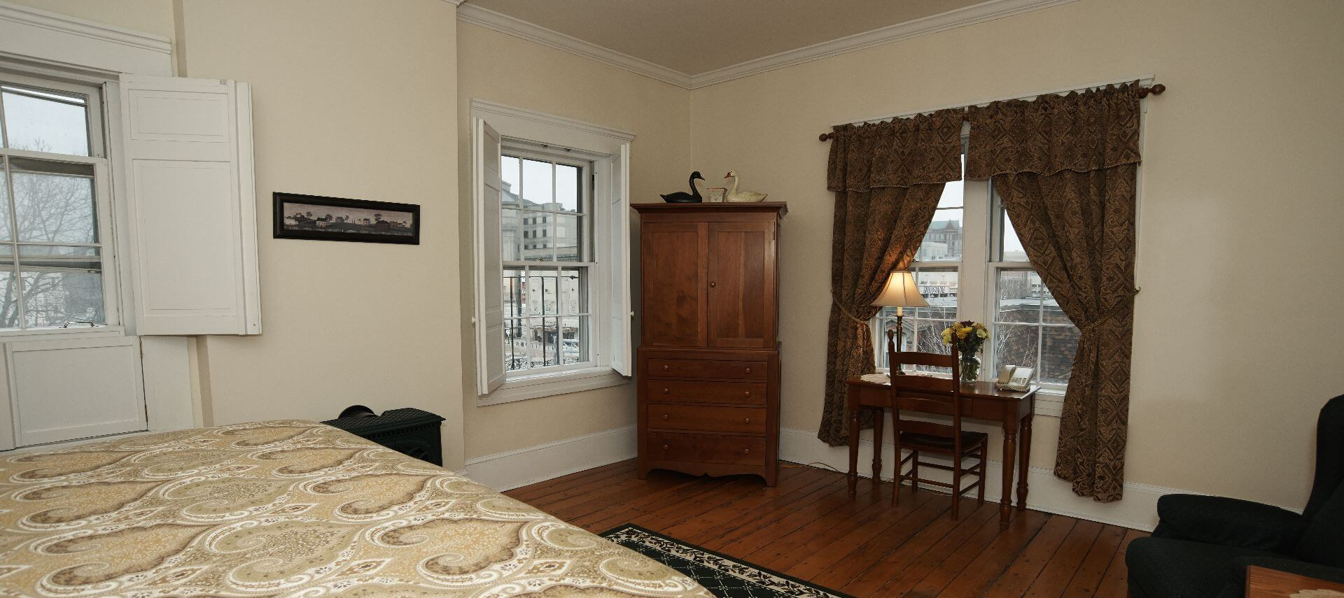 Big bright bedroom with large windows, a wooden armoire and a desk.