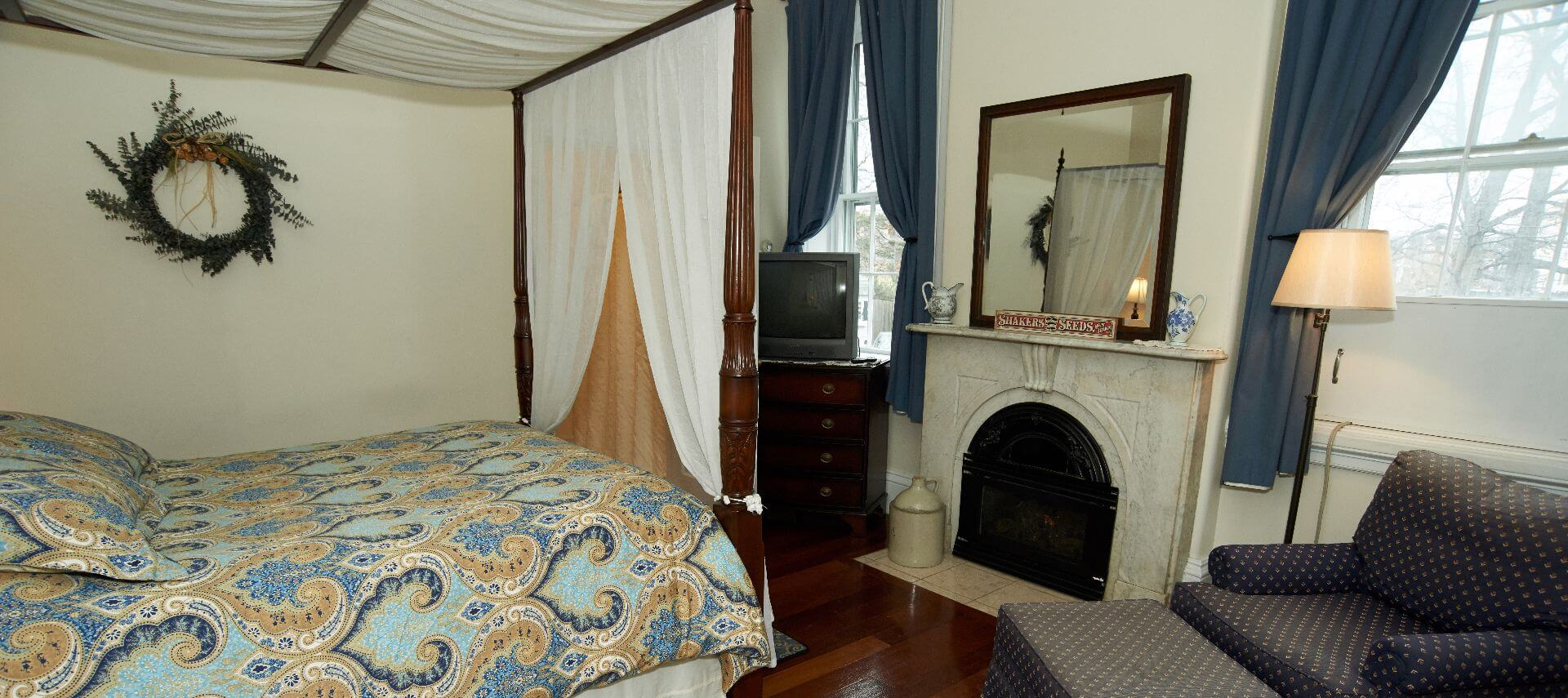 Queen canopy bed faces a white fireplace with a mirror over it and a dresser with a TV.