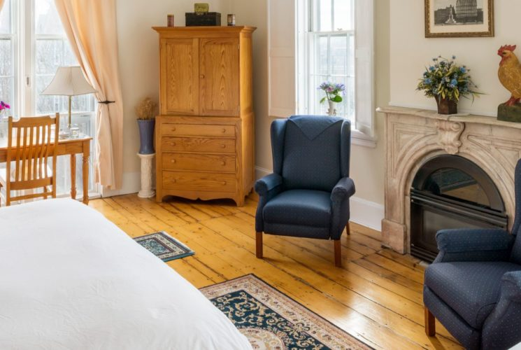 Spacious room with a fireplace and two blue wingback chairs, wooden armoire and desk, small refrigerator, and a king and twin bed.