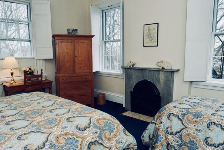 Bedroom with a twin and king bed, a fireplace, a window and a wooden armoire and desk.