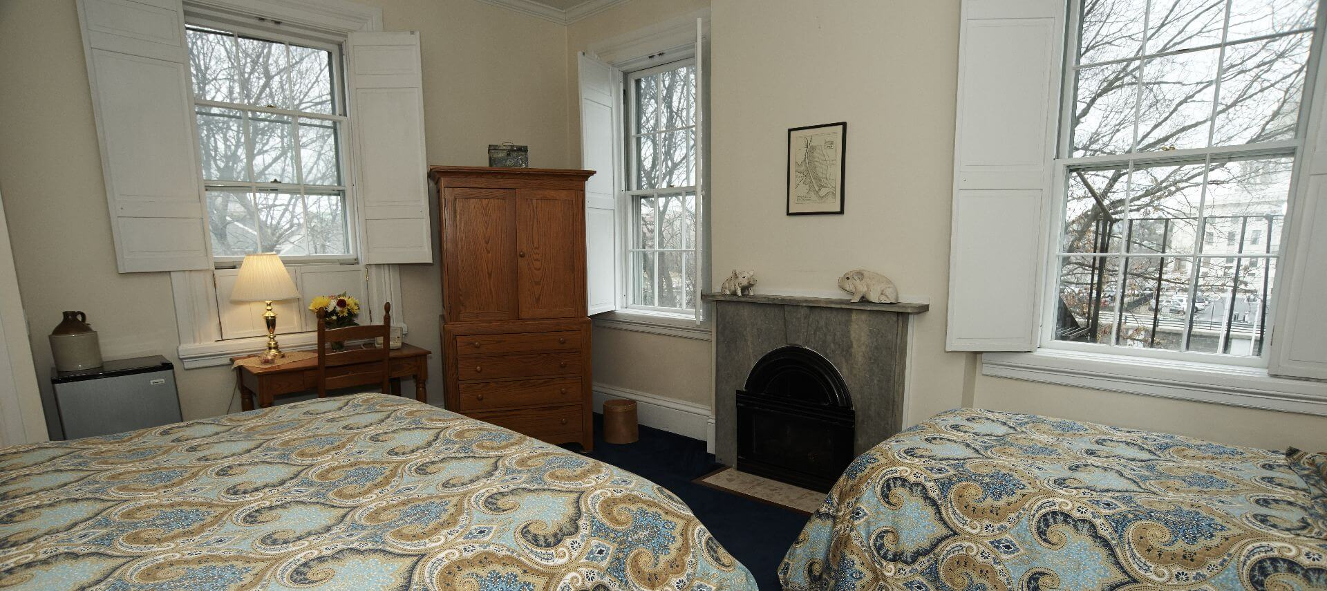 Bedroom with a twin and king bed, a fireplace, a window and a wooden armoire.