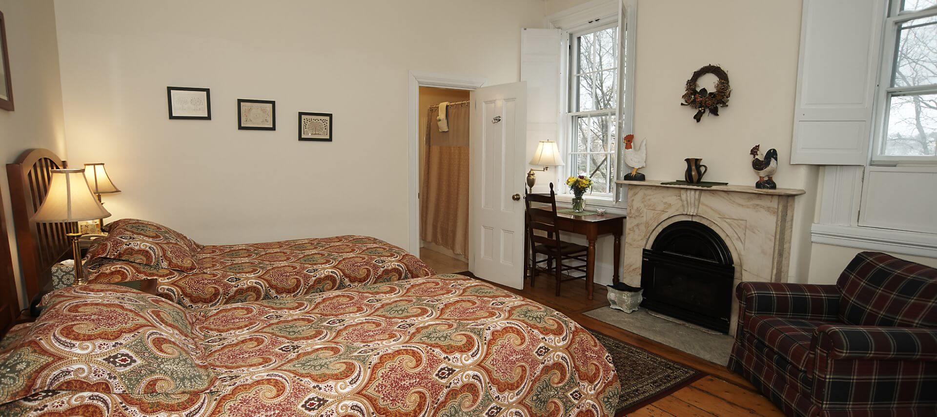 twin beds in a bedroom facing a fireplace, overstuffed chair and large windows.