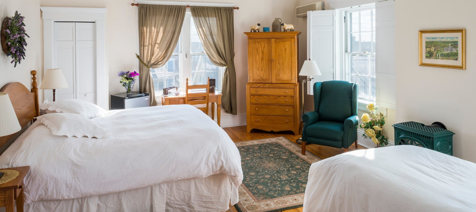 King and twin bed in a room with a wooden desk and armoire, wood stove, and tall windows.