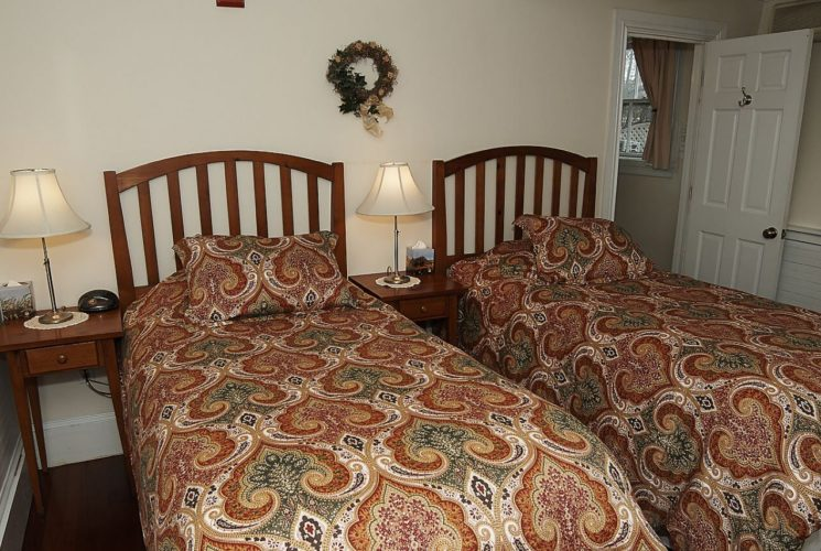 Two twin beds made up in comforters with an ornage and green paisley pattern