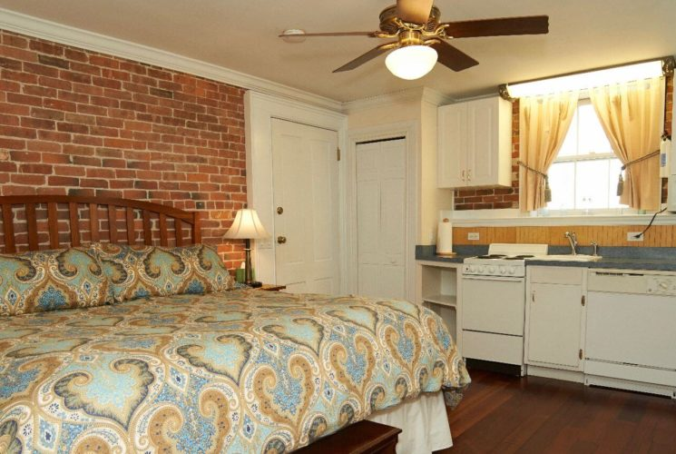 Bedroom with a brick wall, king bed and kitchenette.
