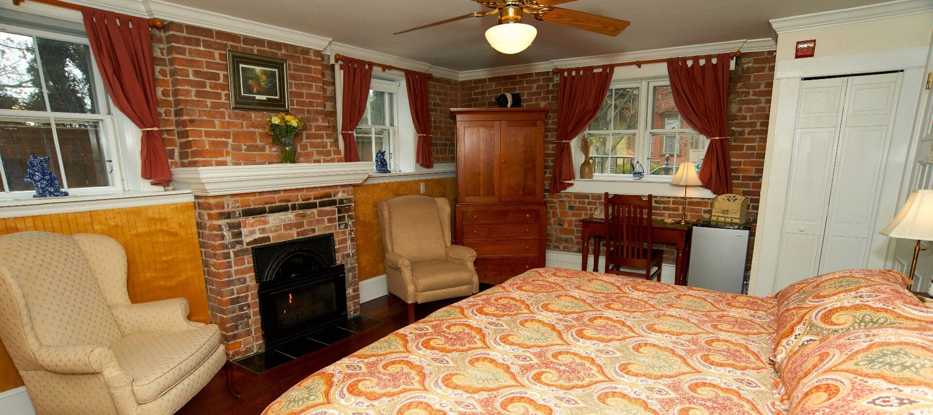 Bedroom with a brick fireplace, king sized bed, wooden armoire, wingback chair and two windows.