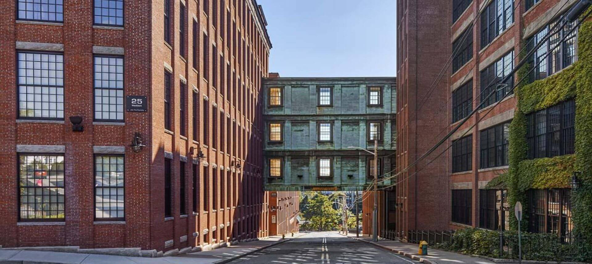 A three-story walk-through hangs between two brick buildings on a city street.