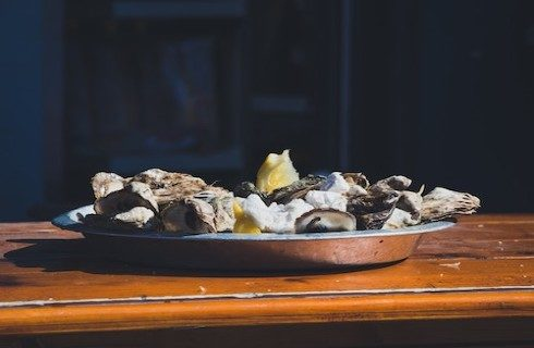 Oysters served on a silver platter with a lemon wedge.