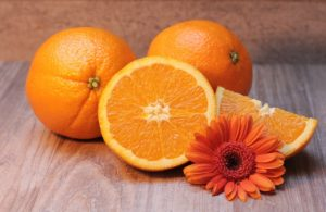 Two whole oranges and a sliced orange displayed on a cutting board with an orange flower.