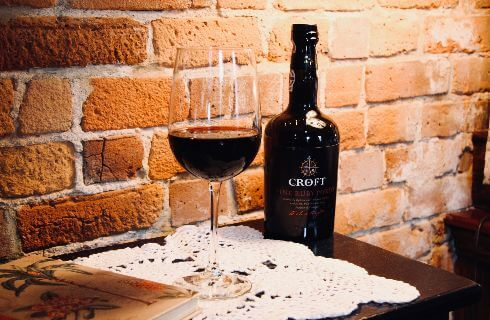 A bottle and glass of red wine rest on a doily-topped wooden table with a brick wall in the background