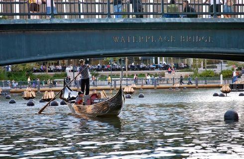A gondolier paddles a gondola under a bridge on the river.