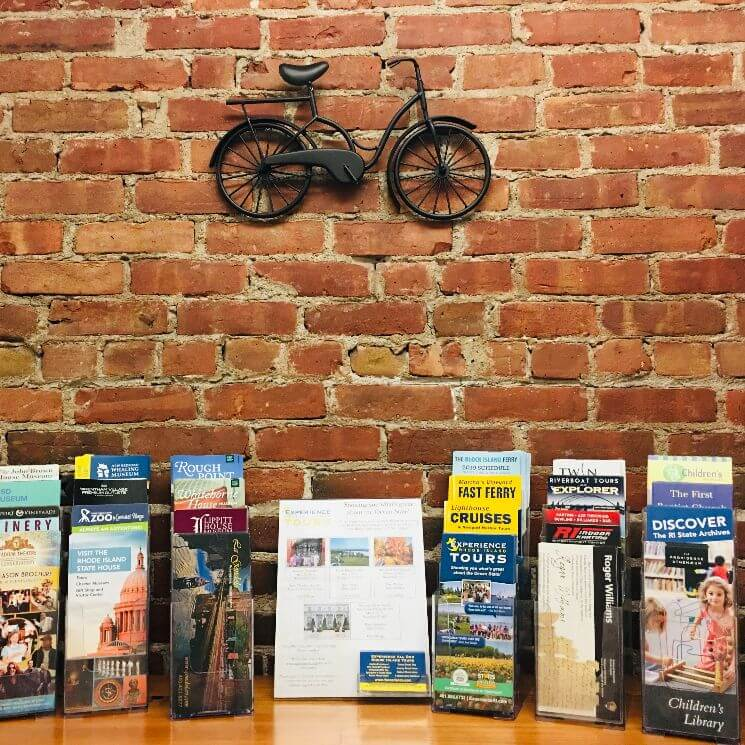 Travel brochures on atable backed by a brick wall and a bicycle sculpture.
