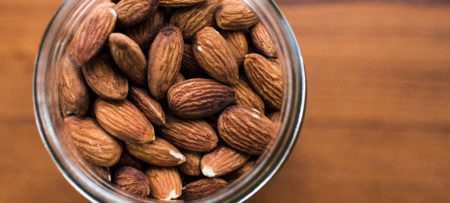 Almonds in a glass jar placed on a tabletop.