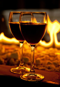 Two glasses of red wine placed in front of a burning fire.