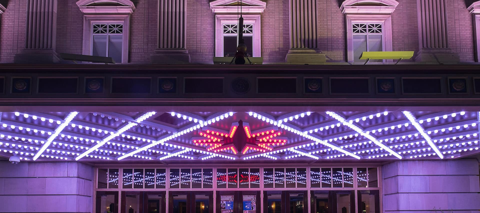 Bright neon white and red lighting of the Veterans Memorial Auditorium exterior .